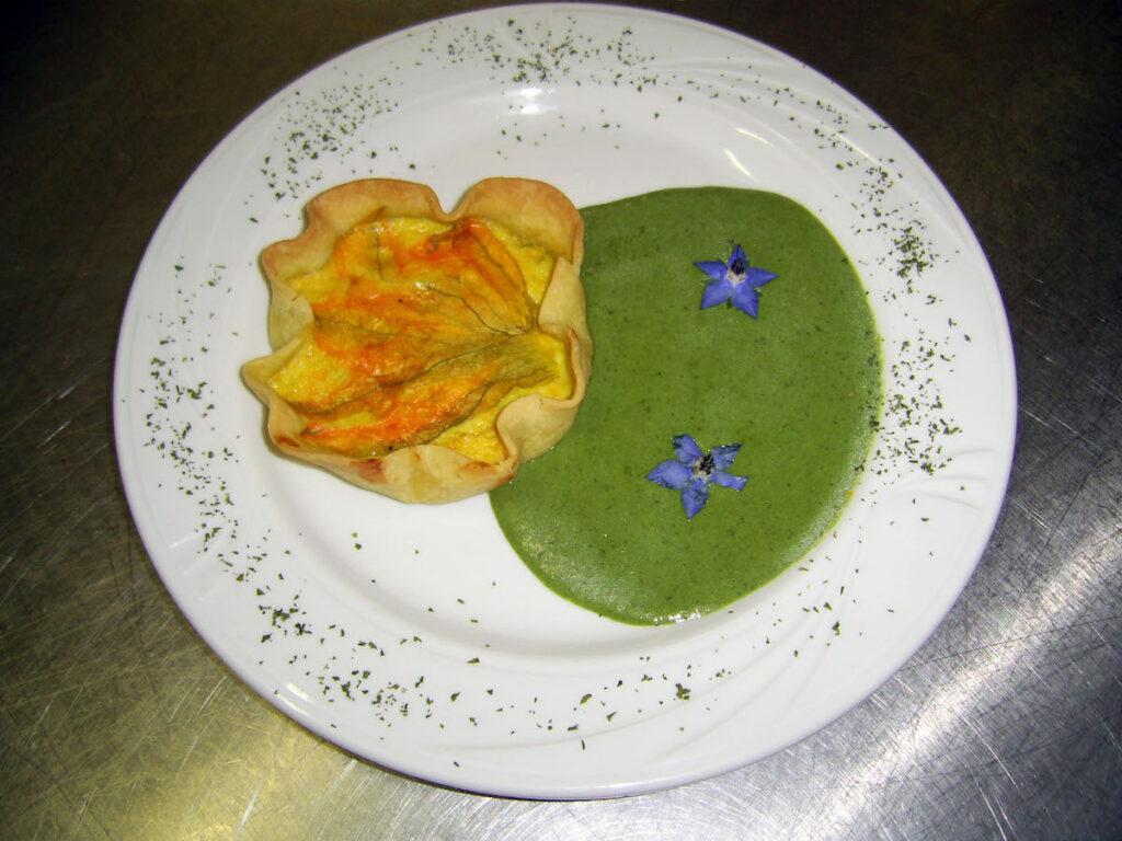 Tortino di fiori di zucchina su crema di borragine